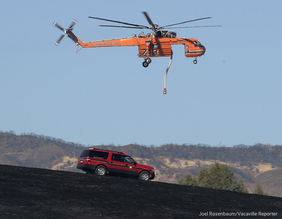 . Vacaville Fire Department Battalion Chief, Gary Mahlberg monitors the progress of a four-alarm grass fire off Olivas Lane in English Hills as a Sikorsky S-64 Skycrane flies overhead to make a water drop on a hot spot Monday in rural Vacaville. Joel Rosenbaum -- The Reporter