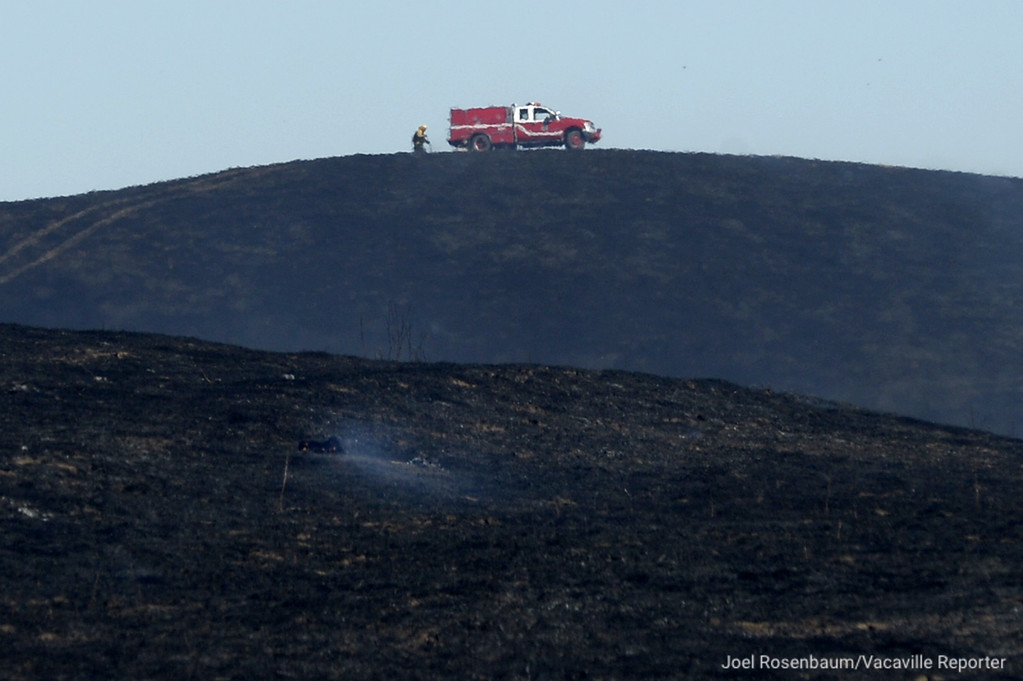. A Vacaville Fire Protection District firefighter attacks a hot spot as crews work to contain a grass fire that swept through English Hills area of rural Vacaville Monday morning burning more than 90 acres. Joel Rosenbaum -- The Reporter