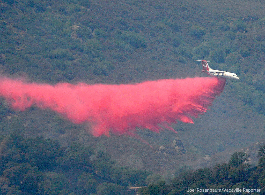 . An air tanker from the California Department of Forestry and Fire Protection (CAL FIRE) makes a fire retardant drop on a hillside Monday, July 2, 2018 above Highway 16 in Brooks, California as crews continue to battle the County Fire which had grown to an estimated 60,00 acres.