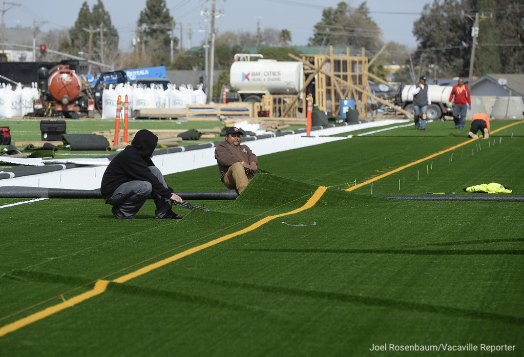 . Workers from Valley Precision Grading continue the Installation of the field turf along the visitors\' sidelines at Wildcat Stadium. Nearly 60,000 square-feet of the turf covers the playing surface and contains material that will keep the field cooler than other field turf.