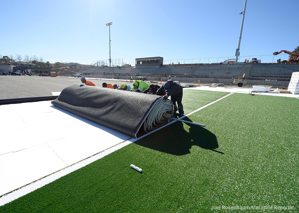 . Workers from Valley Precision Grading roll out some of the first pieces of field turf as construction at Wildcat Stadium Thursday at WIll C. Wood High School. The installation of the 57,600 square-feet of turf is expected to be completed by the end of February. Vacaville School District and Will C. Wood officials are still expected the $16 million stadium to be completed at the end of March or early April.