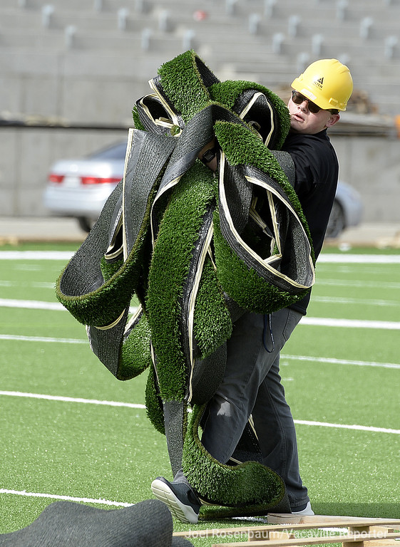 . Austin McLellan, 18 Will C. Wood High School Student Body President  collects discarded strips of field turf from the new Wildcat Stadium that will be cut up and be made into special items that will be sold as a fundraising by student government.