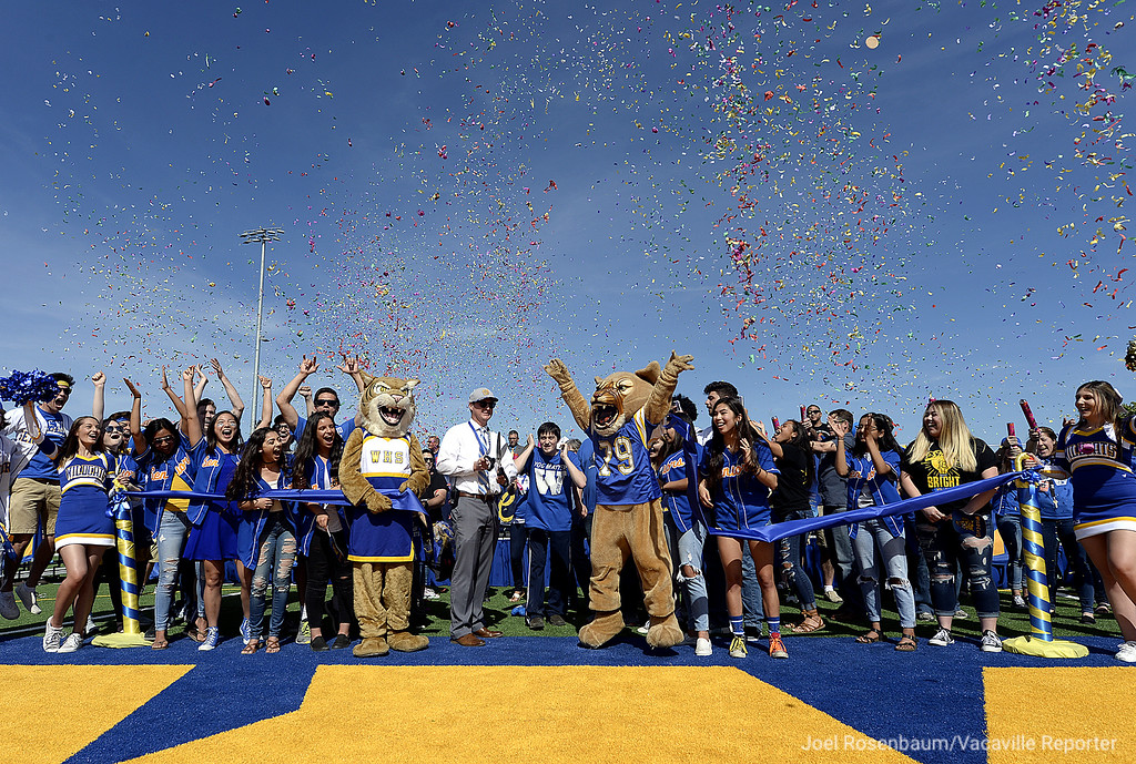 . Surrounded by members of the student body and the school mascots WIll C. Wood High School principal, Adam Rich cuts the ribbon as confetti flies through the air during the grand opening ceremony for Wildcat Stadium Thursday at Wood.