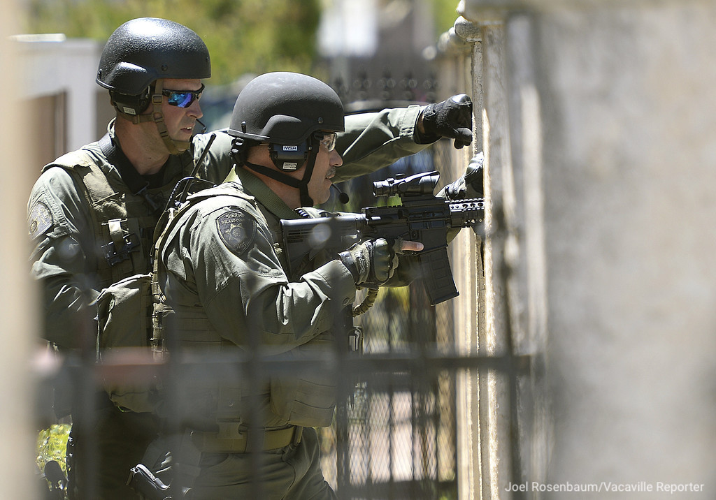 . Mermbers of the Solano County Sheriff\'s SWAT hold their position on the perimeter surrounding an apartment in the 800 block of Delaware Street Monday in Fairfield where a suspect who stole a Toyota pickup truck lead deputies on a short pursuit pursuit and then fled into one of the apartments in the complex.