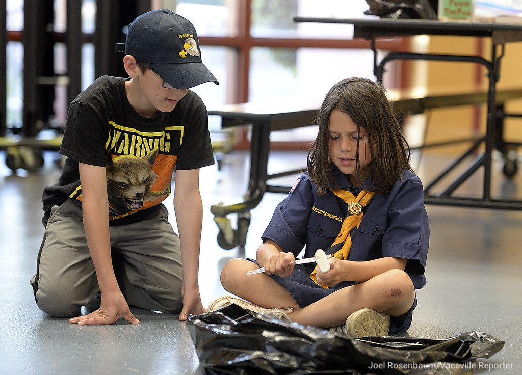 ". Rebecca Rothstein, 7 of Vacaville gets some helpful tips on proper whittling technique from her brother, Aidan, 11 during a den meeting of her Cub Scout pack. Aidan who was a member of the pack by bridged to Boy Scout troop said ""It is cool.\"" that his sister is a cub scout."