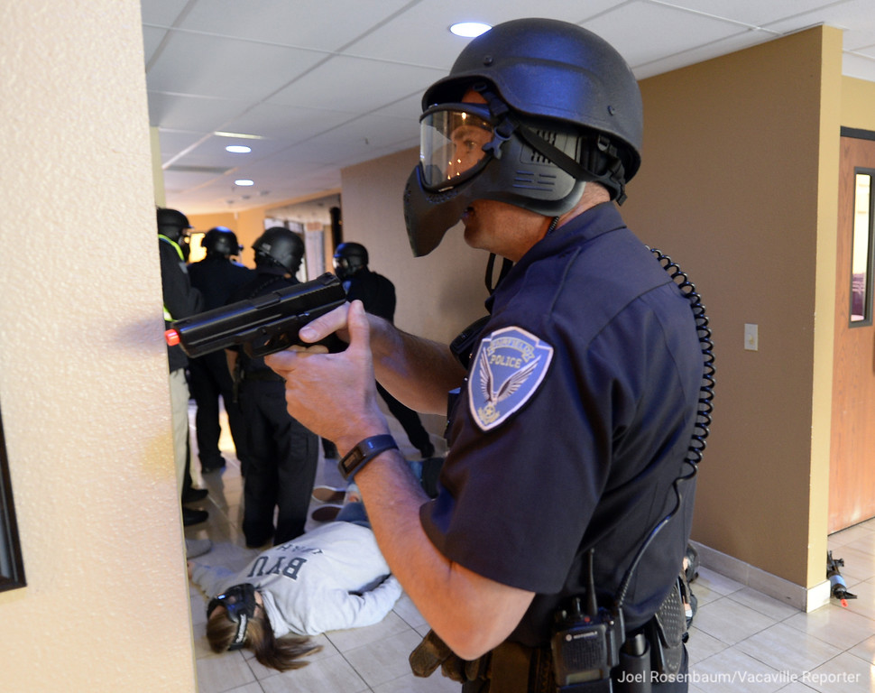 ". A Fairfield Police Officer holds his postition as fellow officers clear a hallway behind him after they neutralized an ""active shooter\"" during a training exercise Tuesday at the Mt. Calvary Baptist Church."