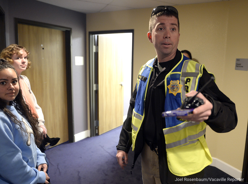 . Fairfield Police Sgt. Josh Kresha coordinates with several students from the Public Safety Academy as they take part in the department\'s emergency preparedness drill Tuesday at Mt. Calvary Baptist Church.
