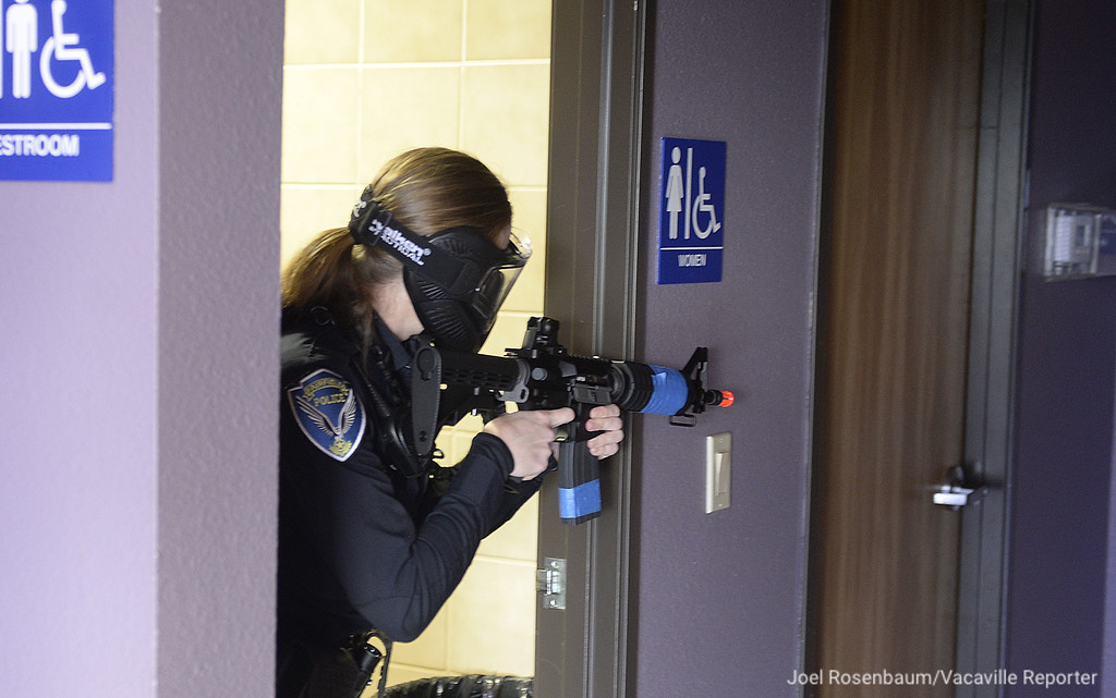 ". A Fairfield Police Officer holds her position as fellow officers clear a hallway behind him after they neutralized an ""active shooter\"" during a training exercise Tuesday at the Mt. Calvary Baptist Church."