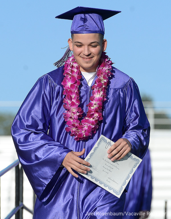 . Country High graduate Mark Ochoa smiles as he reacts to the cheers of his family and friends as he exits the stage after receiving his high school dipolma Thursday at Vaca High.