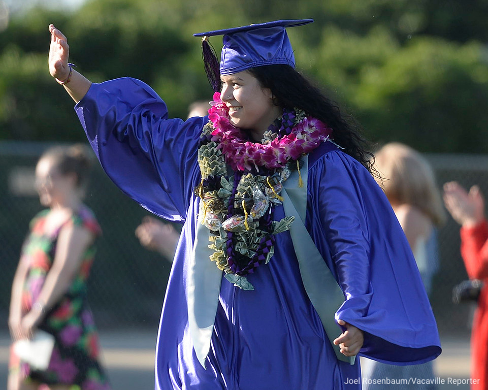 . Country High School graduate. Alexandria Nunez waves to her family and friends as they cheer for her as she walks in procession at the beginning of ceremonies Thursday night at Tom Zunino Stadium.
