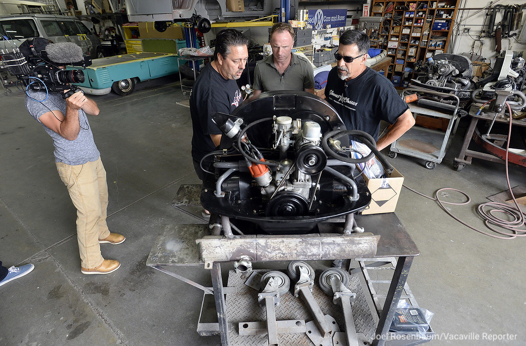 """. Robert Skinner of Vacaville (second from left) describes the rebuilt engine for the new \""""Light Bus\"""" that he and his shop in Vacaville are restoring for documentary about the iconic 1963 Volkwagen Microbus with the show\'s producer and host, John Wesley Chisholm (middle) at his shop in Vacaville. At far left is Chisholm\'s cameraman, Doug Graham and at the far right is Greg Urrutia of Elk Grove who performs most of the engine work for with Skinner."""