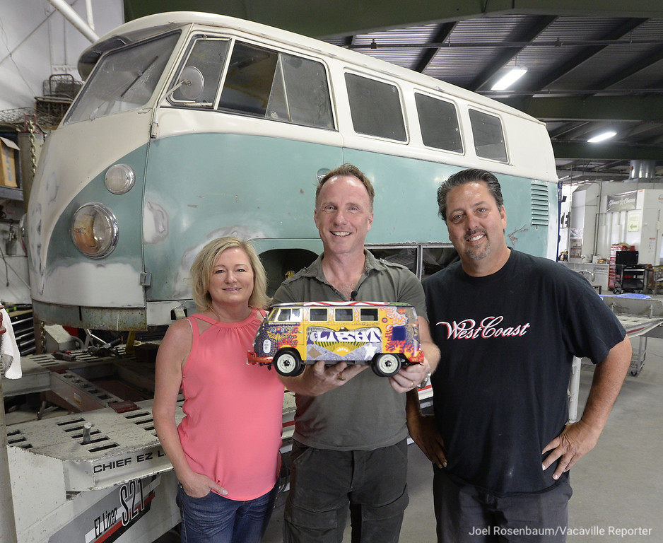. Holding a die-cast model of the iconic 1963 Volkswagen Microbus know as the �Light Bus,� Canadian film maker John Wesley Chisholm (middle) stands with Marlo and Robert Skinner of Vacaville in their auto body shop. Work continues on the restoration of the same model bus (rear) as the original. Once the Skinners� shop finishes the structural and mechanical work on the vehicle, it will be shipped to the East Coast where the artist who painted the original van will paint this one. The replicated bus will eventually show up at the 50th anniversary of Woodstock in August 2019.