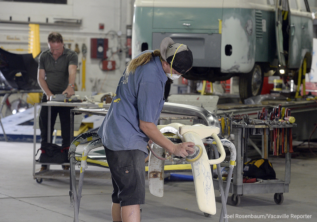 """. Dillion Skinner of Vacaville sands down the front bumper of a 1963 Volkswagen Microbus while work continues on the restoration of a the vintage vehicle. The VW bus is the exact same model as the iconic \""""Light Bus\"""" that was made famous at Woodstock in 1969. Skinner along with his father Robert and others in the shop are working with John Wesley Chisholm (rear) a filmmaker from Canada who is working on a program about the search for the original bus and then the restoration of this bus that was discovered in Palo Alto a month ago."""