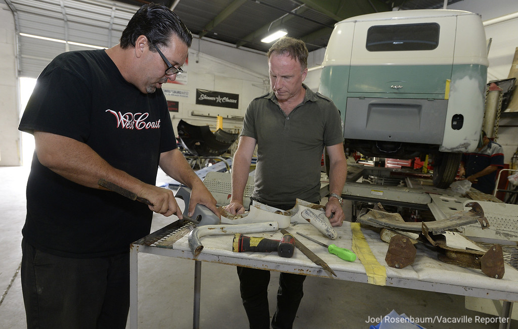 """. Robert Skinner of Vacaville shows John Wesley Chisholm one of the rear bumper that will be placed on the 1963 VW Microbus that they are working to restore so it can be transformed into an accurate representaton of the iconic \""""Light Bus\"""" that was made famous at Woodstock in 1969."""