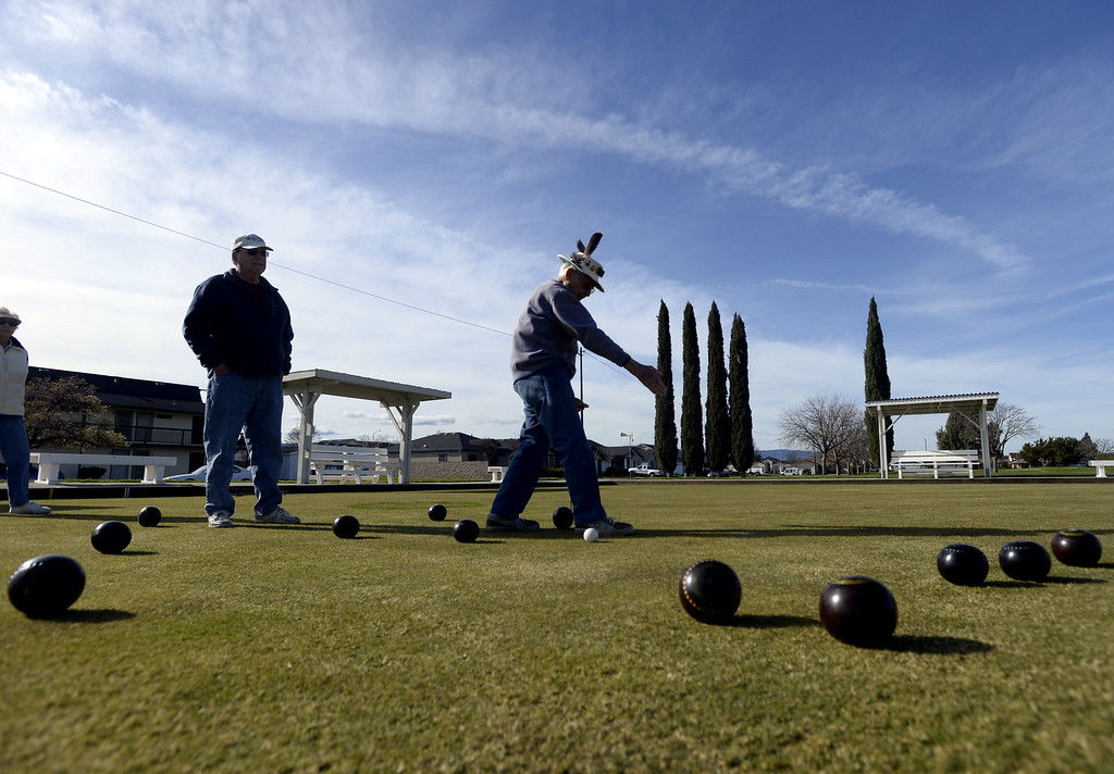 . Leisure Town Lawn Bowling Club member, Dick Ruddy, 89 of Vacaville points out the best path for his teammate to roll his bowl.  Joel Rosenbaum -- The Reporter