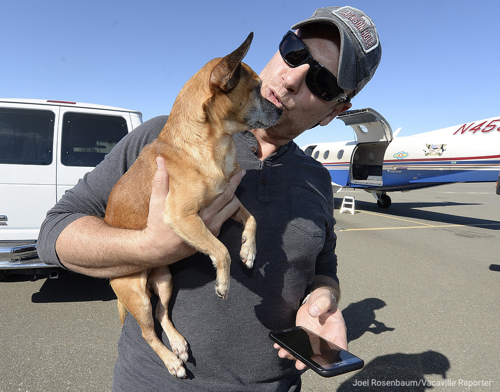 . Damian Cross with Wings of Rescue (left)  visits with one of the nearly 40 dogs that he will be transported from the Nut Tree Air Port to a shelter in Montana. Wings of Rescue, a non-profit based in Southern California works with shelters to transports endangered shelter animals either by overcrowding or other reasons to shelters with space available.