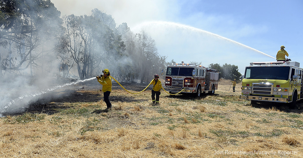. Firefighters from the University of California, Davis Fire Department (front) attack a small grass fire as a Dixon firefighter (rear) uses a deck gun to attack one of two buildings burning on a property along Bulkley Road Monday as the battle a two-alarm structure fire.