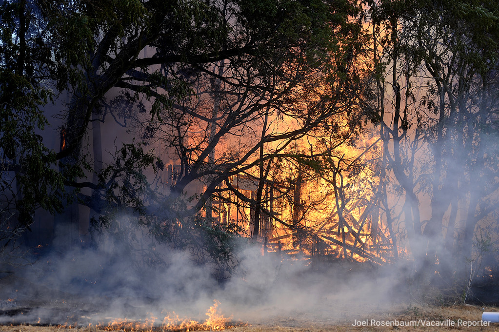. Flames consumes one of two structures on a property along Bulkley Road Monday in rural Dixon. About 25 firefighters from six different agencies from Solano and Yolo Counties battled the blaze whose origin and cause are currently under investigation.