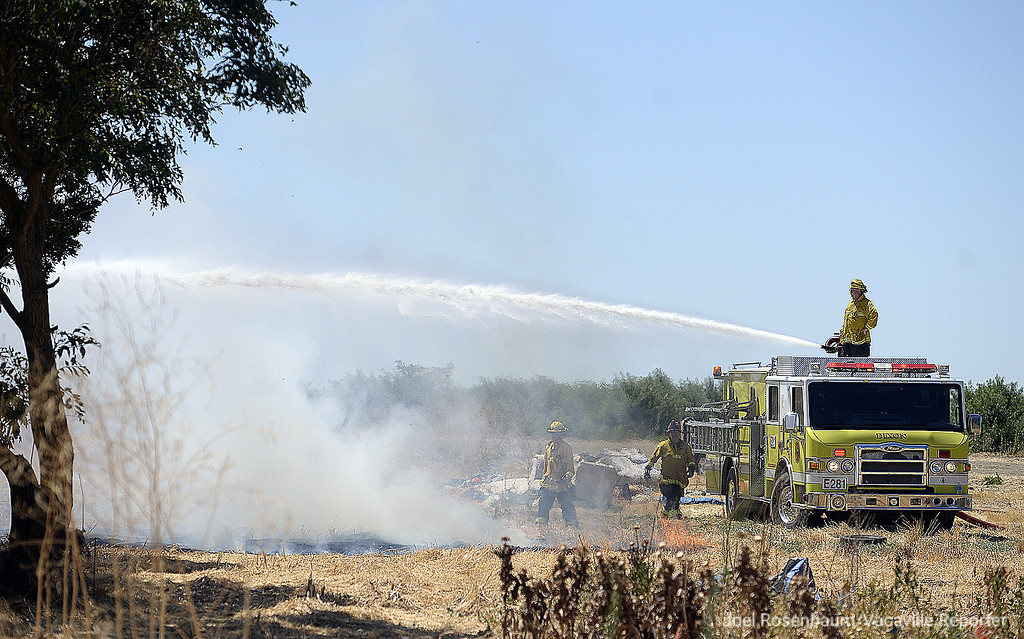 . A Dixon firefighter  uses a deck gun to attack one of two buildings burning on a property along Bulkley Road Monday as the battle a two-alarm structure fire.