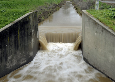 Water rushes through the Ulatis Creek Spillway at Leisure Town Road early Monday afternoon. Joel Rosenbaum -- The Reporter