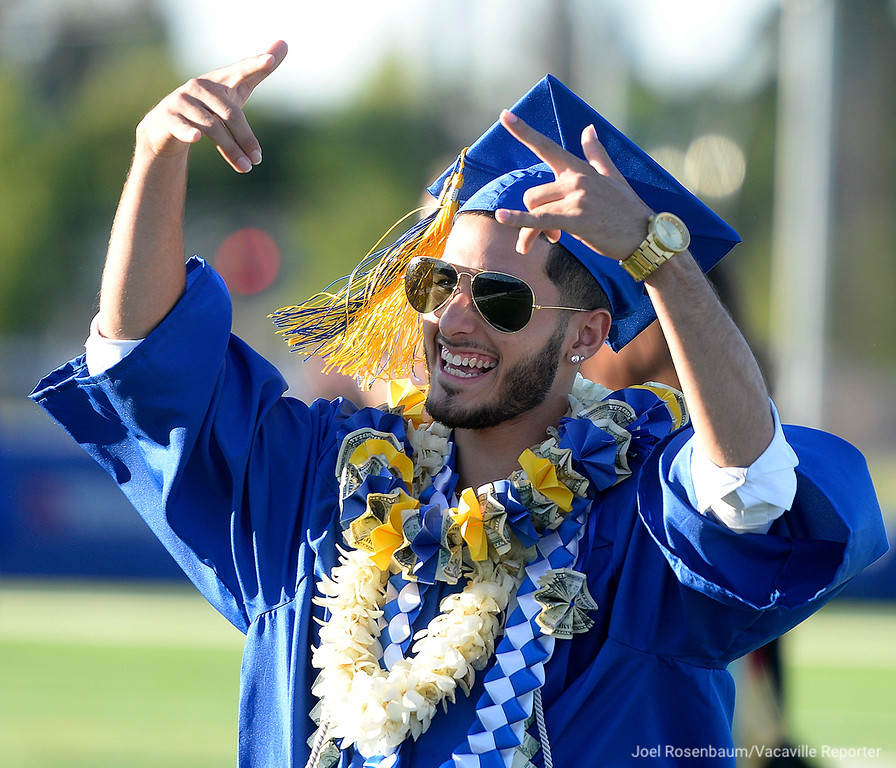 . Will C. Wood High graduating senior, Andrew Singh waves to his family and friends as the cheer for him as he walks in procession during commencement ceremonies Friday at WIldcat Stadium. For the first time in the school\'s nearly 30 year history as a high school the students were able to graduate on their own campus.