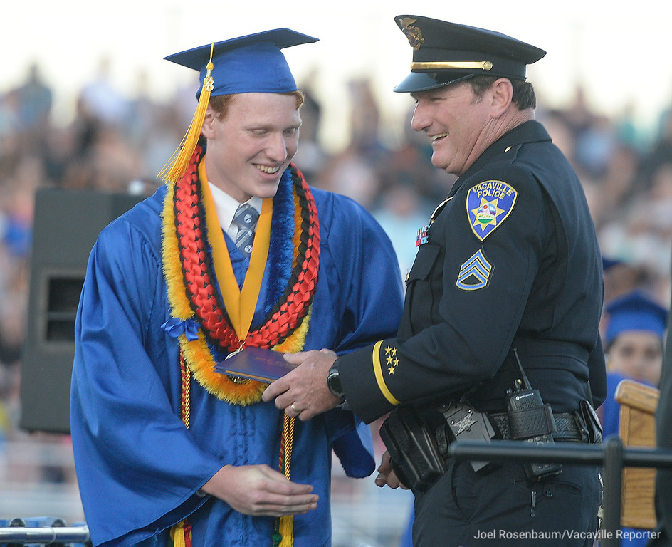 . Will C. Wood High School Valedictorian, Jonathan Dye (left) receives his diploma from his father Vacaville Police Sgt. Todd Dye during graduation ceremonies Friday at Wood. Sgt. Dye who was in charge of the department\'s youth services unit was a big presence on campus and retired from the department on the same day his son graduated.