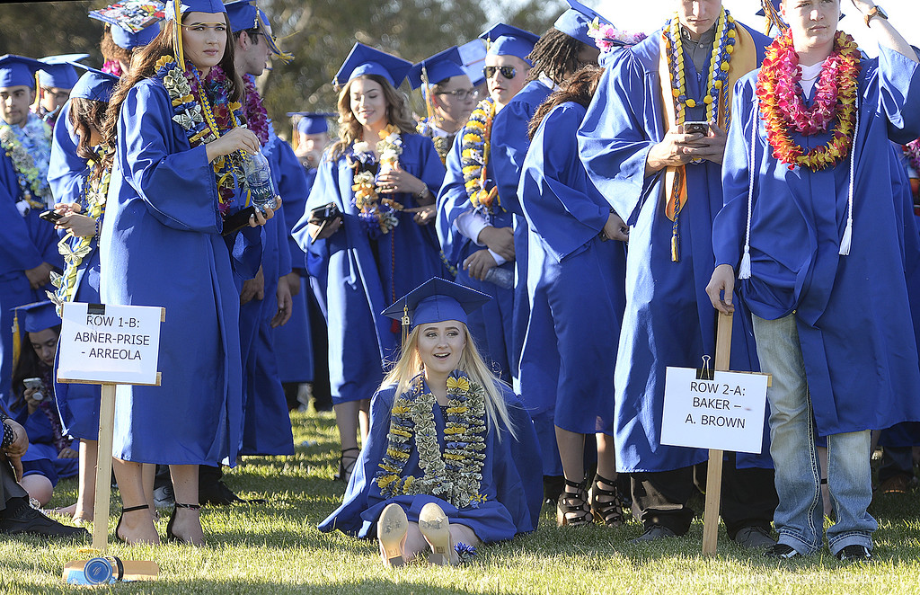 . Will C. Wood graduating senior, Jade Balasia takes a load of her feet as she waits with her fellow classmates to begin commencement Friday at Wood.