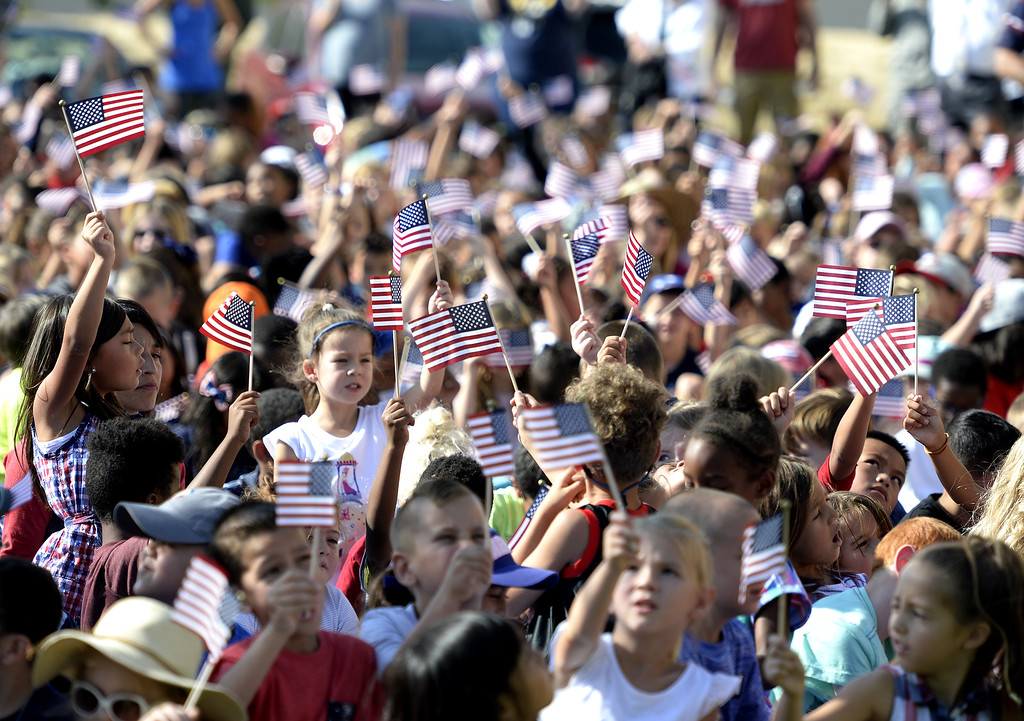. Students from Scandia and Travis Elememtary Schools on Travis Air Force Base wave American Flags at the conclusion of the 11th Annual 9/11 Freedom Walk Monday at the Airman and Family Readiness Center on Travis Air Force Base. Students from both schools walked from their campuses to the center to honor the memories of the victims and survivors of 9/11. Joel Rosenbaum -- The Reporter