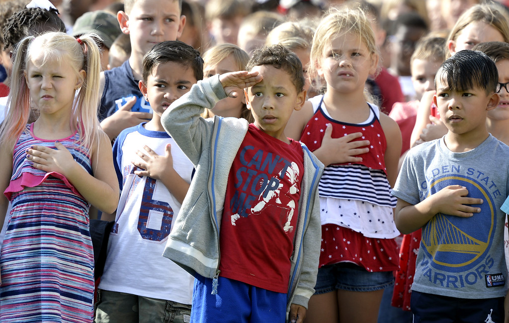 . First grade students from Scandia Elementary School honor the flag as the national anthem is played at the beginning of the 9/11 Freedom Walk Ceremony Monday at the Airman and Family Readiness Center on Travis Air Force Base. Students from Travis and Scandia Elementary School walked from their campuses to the center to honor the memories of the victims and survivors of 9/11. Joel Rosenbaum -- The Reporter