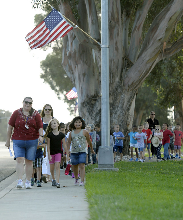 . Students at Scandia Elementary School on Travis Air Force Base walk together along Travis Blvd. to the Airman and Family Readiness Center during the 11th annual Freedom Walk Monday on base. The annual event honors the memory of those who were killed and others effected by the tragic events 16 years ago. Joel Rosenbaum -- The Reporter