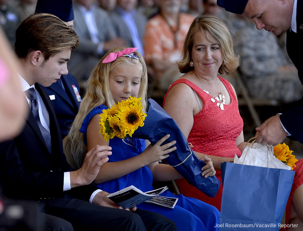 . Megan Klein, 9 (middle) receives a bouquet of flowers from her father, United States Air Force Colonel John M. Klein as she sits with her mother, Anji (right) and brother Sam, 17 during a Change of Command Ceremony Tuesday at Travis Air Force Base. Col. Klein will be starting a new assignment at Council of Foreign Relations in New York after serving as commander of the 60th Air Mobility Wing at Travis for the past two years.