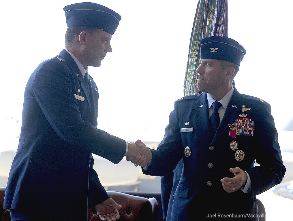 . United States Air Force Colonel Ethan C. Griffin., new commander of the 60th Air Mobility Wing is congratulated by outgoing commander, Col. John M. Klein Jr. after he received the unit guidon and assumed command of the wing Tuesday during a Change of Command Ceremony at  Travis Air Force Base.