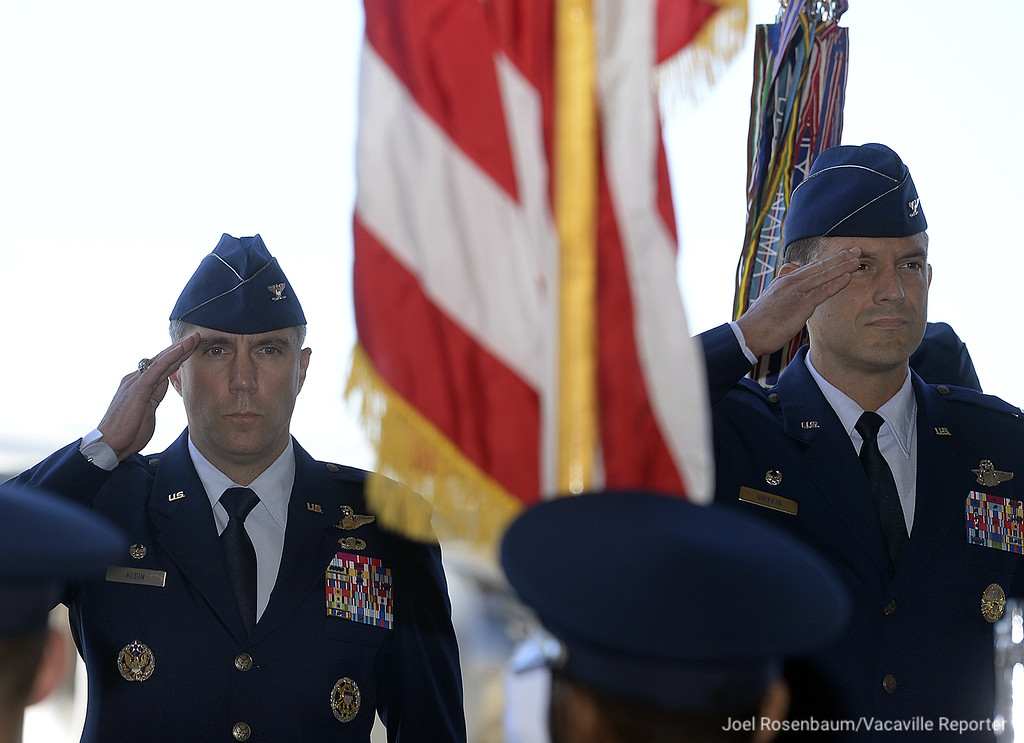 . United States Air Force Colonel John M. Klein, Jr., the outgoing commander of the 60th Air Mobility Wing (left) and incoming base commander, Col. Ethan C. Griffin both salute as the national anthem is played during a Change of Command Ceremony Tuesday at Travis Air Force Base in Fairfield.