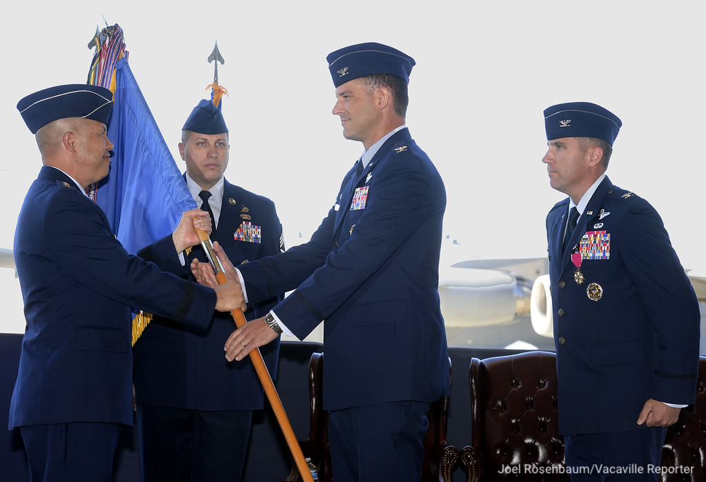 . United States Air Force Lt. General Giovanni K. Tuck, commander 18th Air Force hands off the unit guidon to Colonel Ethan C. Griffin as he officially takes command of the 60th Air Mobility Wing at Travis Air Force base during a Change of Command ceremony Tuesday on base. Col. Griffin assumes command from Col. John M. Klein Jr. (right) who received an assignment at the Council of Foreign Relations in New York City.