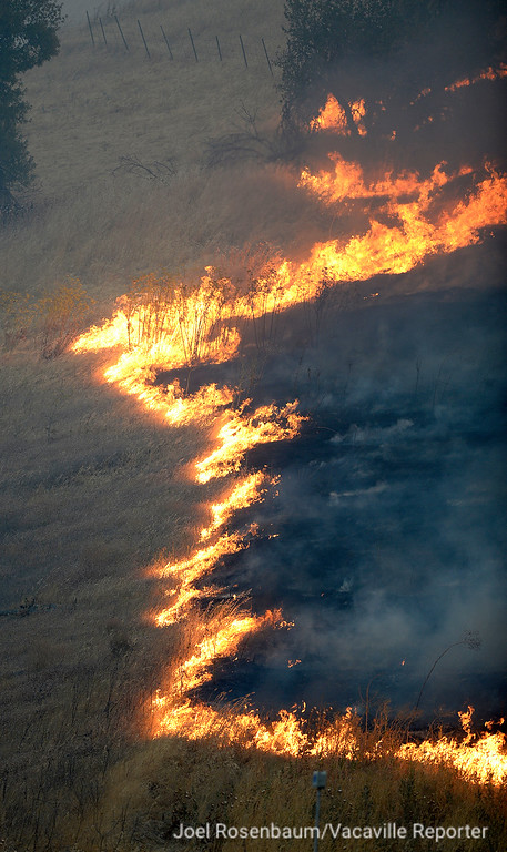 . Flames burn in the hillside above Discovery Way Friday in Fairfield during the 1,000 acre Nelson Fire.