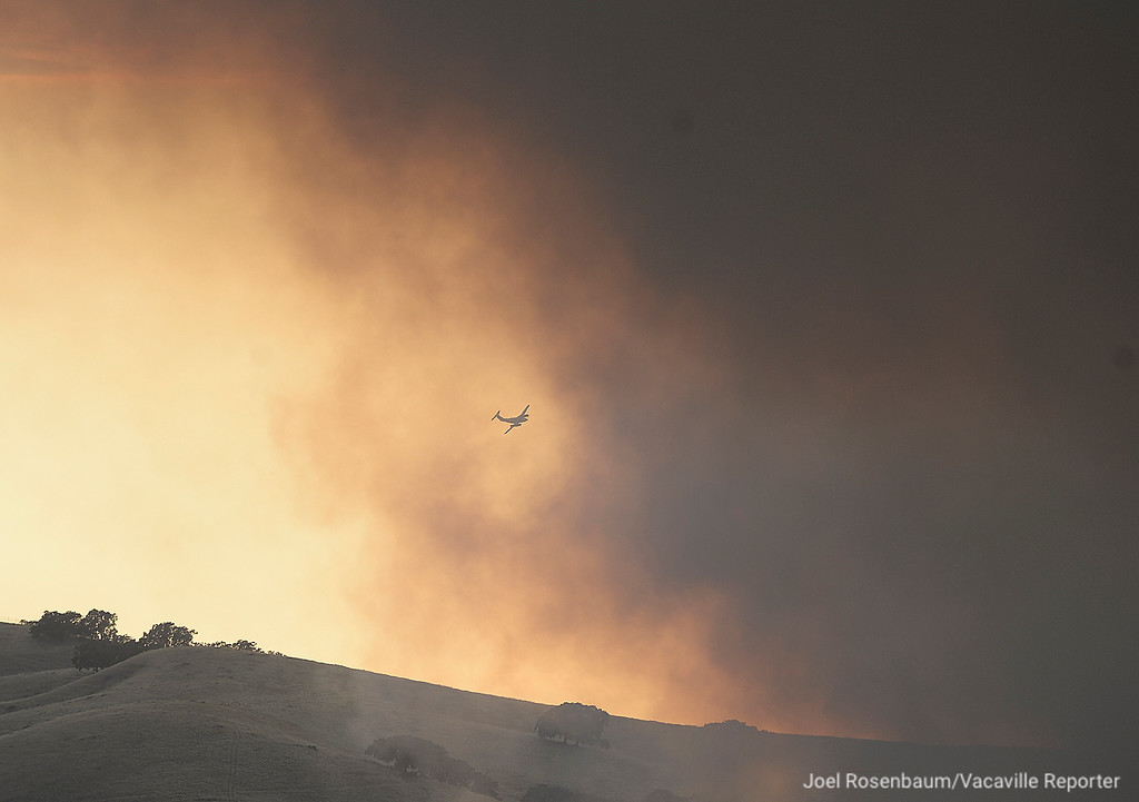 . A spotter plane from the California Department of Forestry and Fire Protection flies over the hills above the California Medical Facility Friday as smoke billows into the air from the 1,000 acre Nelson Fire.