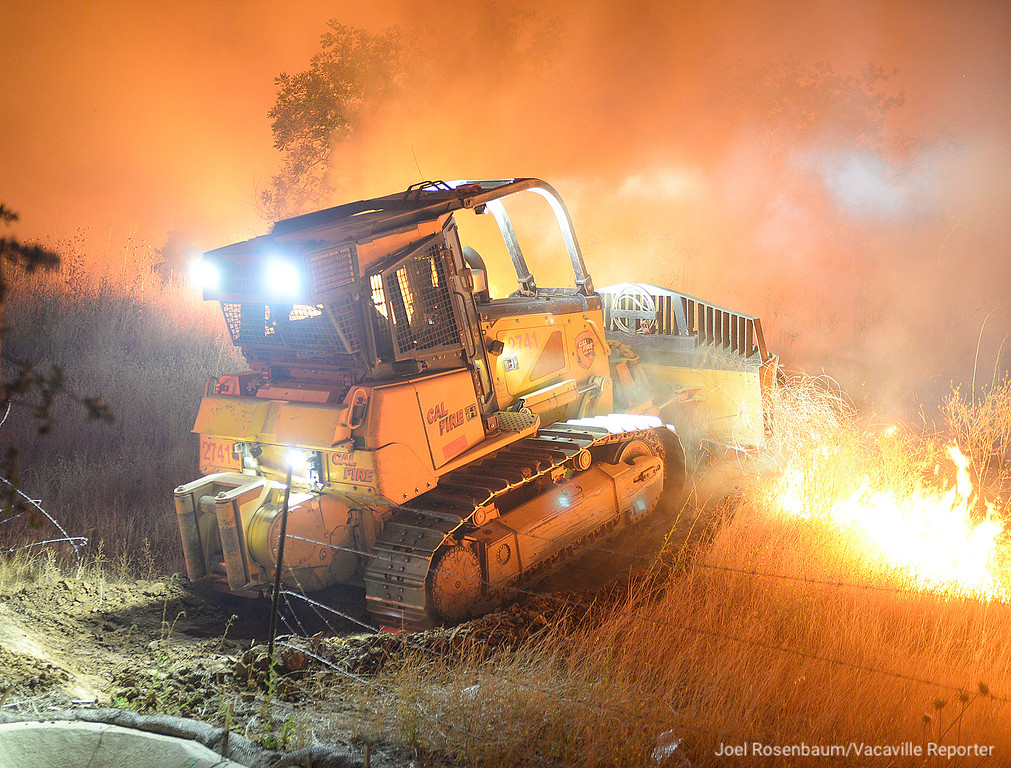 . A bulldozer from the California Department of Forestry and Fire Protection cuts a fire break in the hills above Discovery Way in the Gold Ridge subdivision Friday evening.