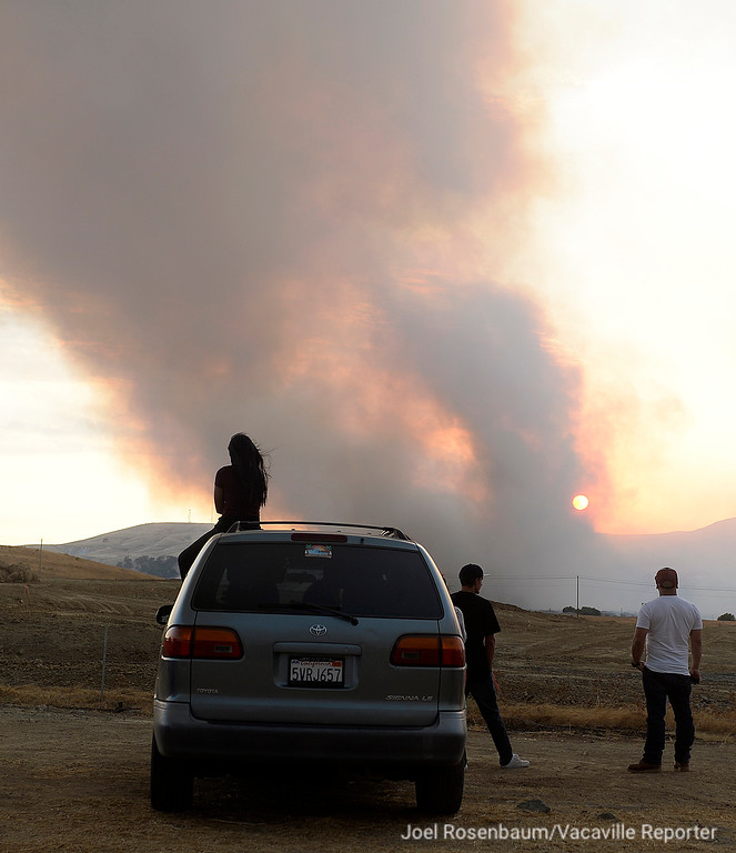 . People stopped along Vanden Road between Vacaville and Fairfield watch as smoke from the 1,000 acre Nelson Fire  billow into the skies above early Friday evening.