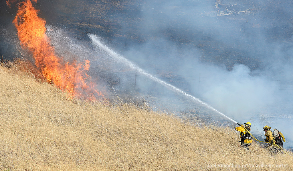 . Firefighters from the Vacaville Fire Department make an attack on a flare up on the hillside above eastbound Interstate 80 near Nelson Road. The 1,000 acre grass fire that started along the freeway and burned between Vacaville and Fairfield.