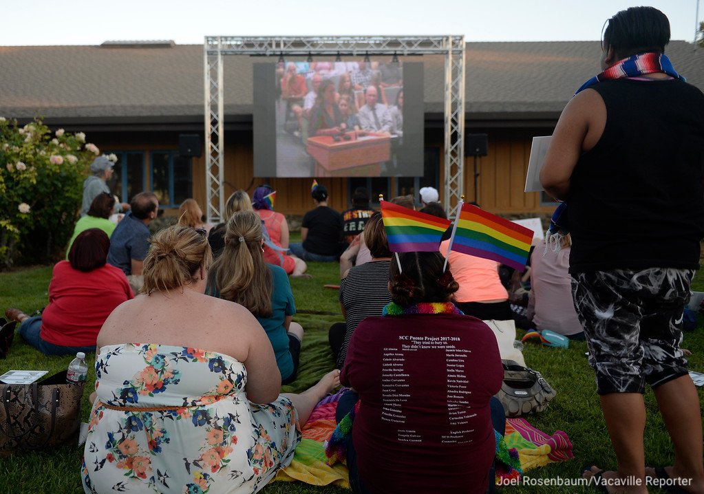 . With the council chambers filled to capacity, protestors gather outside of Dixon City Hall watch the Tuesday\'s city council meeting on a big screen set up on the lawn.