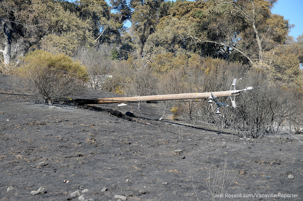 . A power pole damaged by fire lays on its side in a charred field at the fire at the top of Twin Sisters Road in rural Solano County. Joel Rosenbaum -- The Reporter