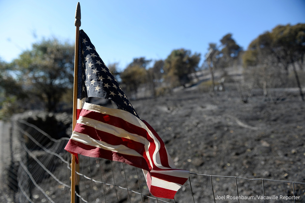 . A tattered American flag attached to fence at the end of Twin Sisters Road waves in the light breeze Thursday. The area was the first hit by the Atlas Fire when it entered Solano County early Tuesday evening. Joel Rosenbaum -- The Reporter
