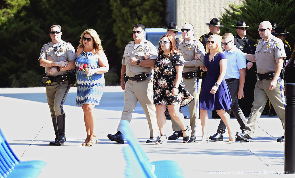 . Keri Griess (left) is escorted to her seat along with her children, Kaci, Kadi and Kole at the beginning of a bell toll tribute Monday in West Sacramento for her husband and their father, Kirk an officer in the Solano County office that was killed last Friday will he was on a traffic enforcement stop on westbound Interstate 80 in Fairfield.