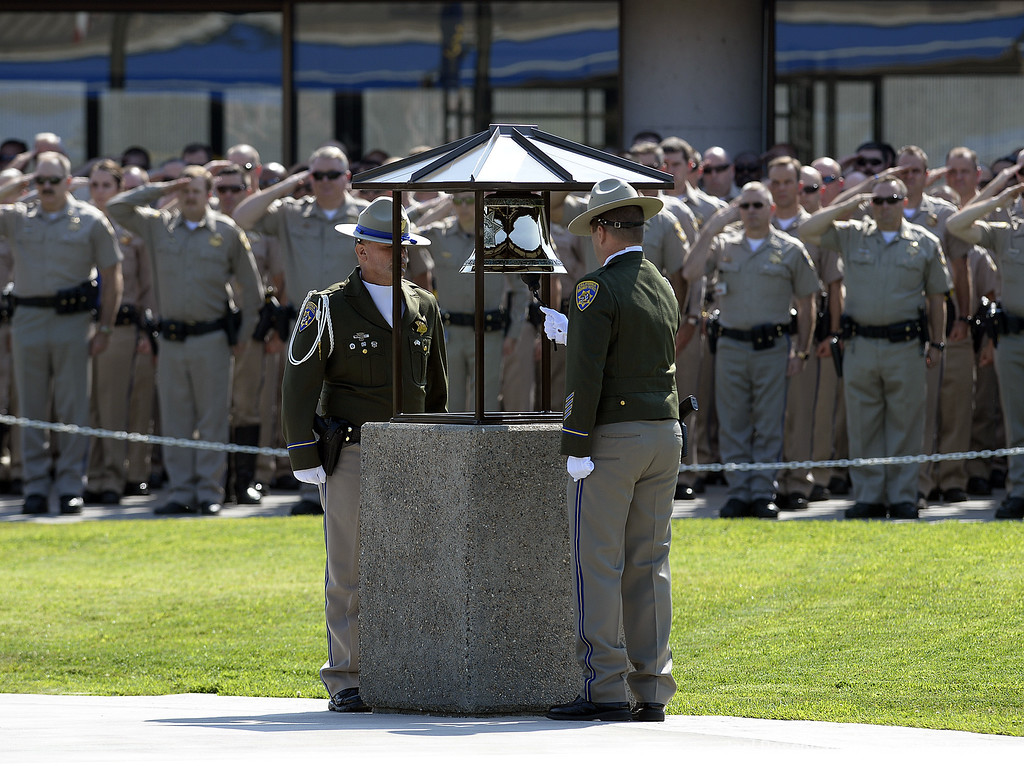 . California Highway Patrol Honor Guard members, officer Michael Paulson (left) and Christopher Wahl perform a bell toll tribute for fellow officer Kirk Griess Monday at the CHP Academy in West Sacramento. Griess was killed last Friday in Fairfield while on a traffic enforcement stop on westbound Interstate 80.