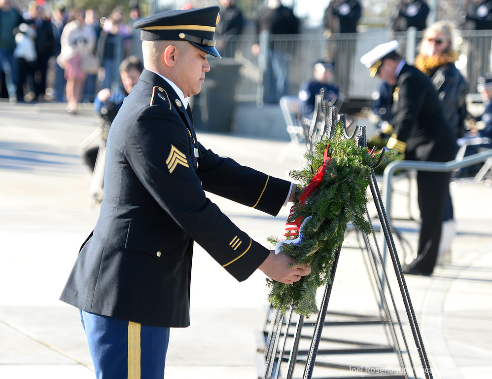 . A member of the United States Army places a wreath  honoring their fellow service members who are during at the Sacramento Valley National Cemetery during the Wreaths Across America Ceremony Saturday in Dixon.