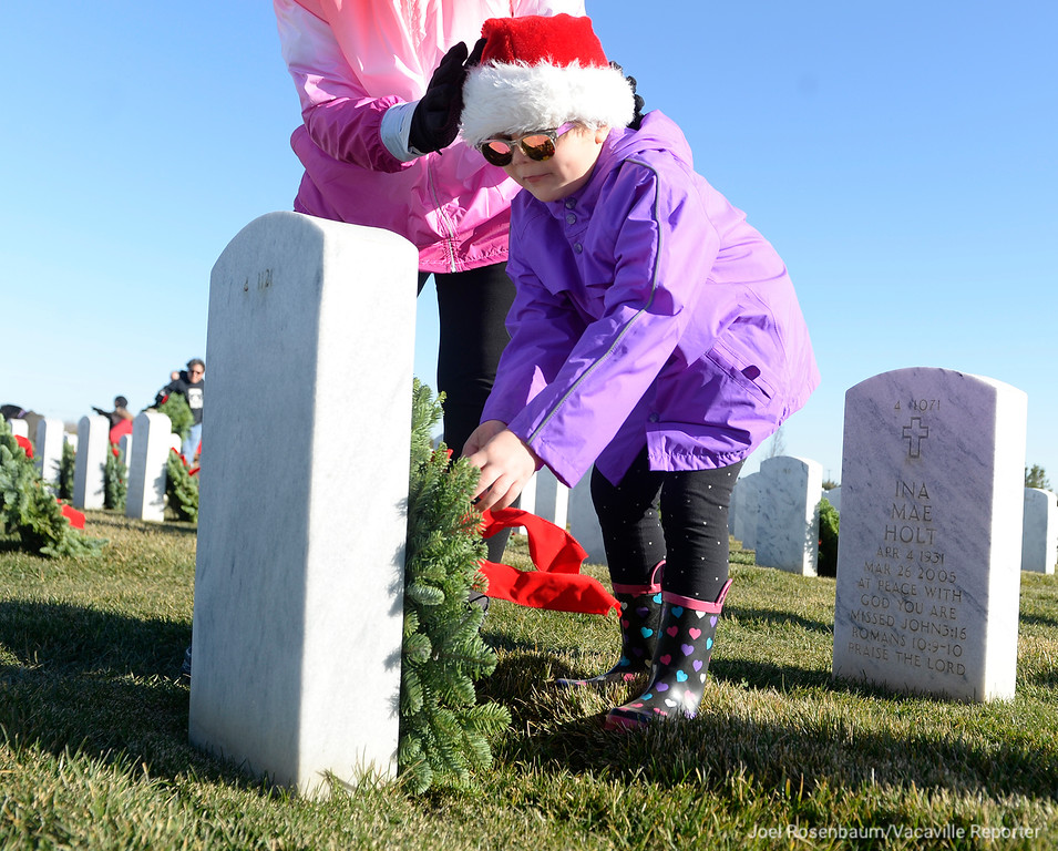 . Jasmyne Krystek, 5 of Vacaville places a wreath on a headstone at the Sacramento Valley National Cemetery in Dixon, California on Saturday, as he participates in Wreaths Across America.