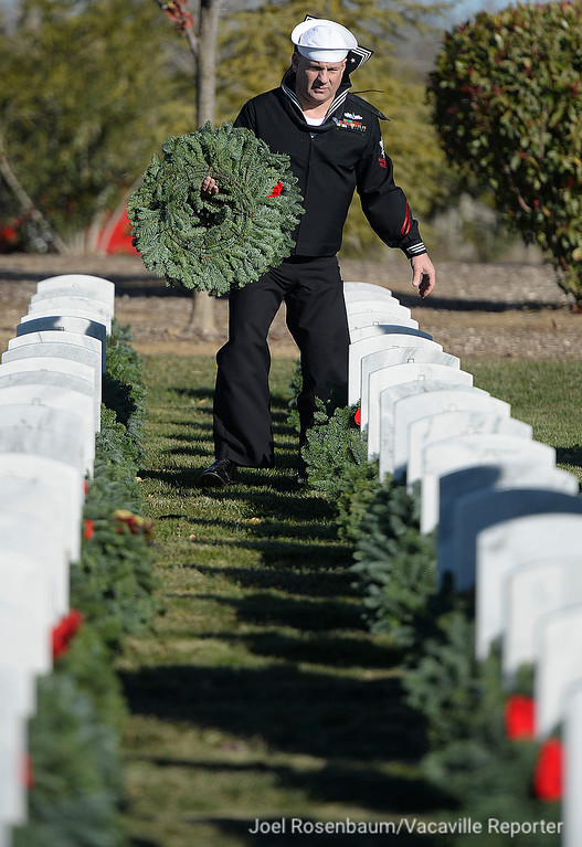 . United States Navy hospital corpsman Scott Ott places a wreath on a headstone at the Sacramento Valley National Cemetery in Dixon, California on Saturday, as he participates in Wreaths Across America.
