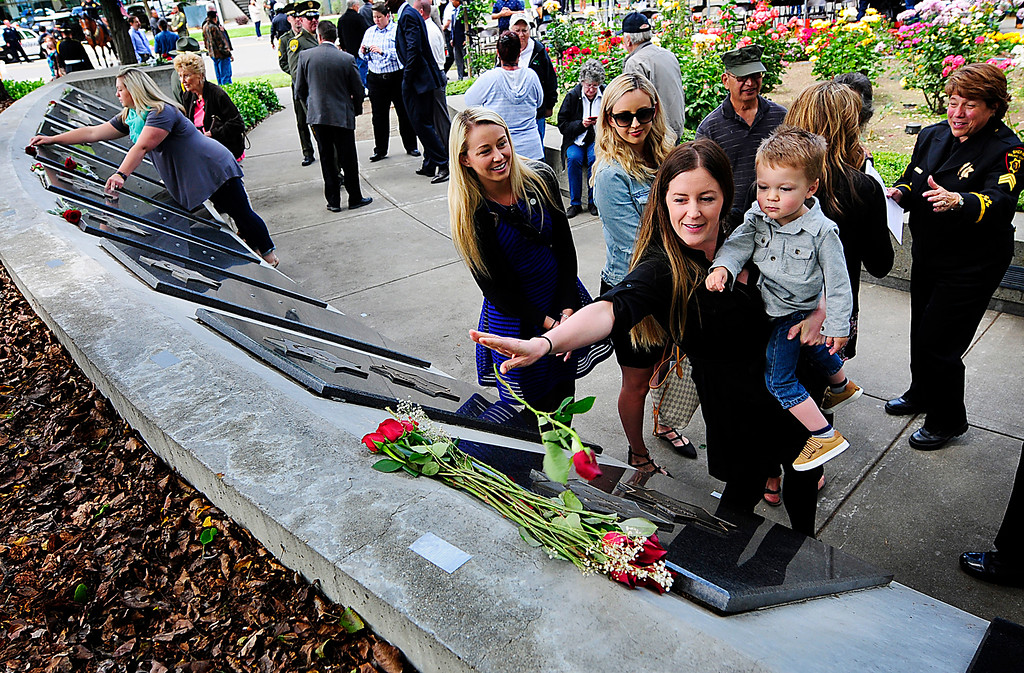 . FAIRFIELD, CA - MAY 16, Jillian and James Diaz toss a roses on to the Peace Officers\' Memorial wall above the the star of Jillian\'s dad and James\' grandpa, Vallejo Police Officer Jim Capoot during the Remembering the Fallen 2018 Peace Officers\' Memorial Service in Fairfield on Wednesday.(Chris Riley/Times-Herald)