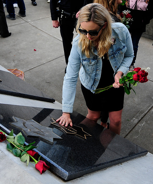 FAIRFIELD,, CA - MAY 16, Jamie Trujillo touches the star on her father's memorial, Vallejo Police Officer Jim Capoot, during the 2018 Peace Officers' Memorial Service on Wednesday in Fairfield. (Chris Riley/Times-Herald)