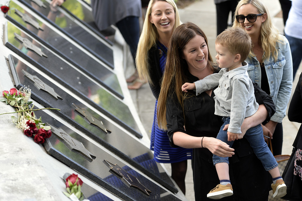 . Along with her sisters, Justine Capoot (left rear) and Jamie Trujillo (middle,) Jillian Diaz of Vacaville holds her son, James, 2 as they stand next to the memorial star that bears the name of their father and his grandfather, James, a Vallejo Police Officer who killed in the line of duty in November of 2011. Joel Rosenbaum -- The Reporter